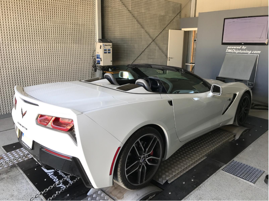 White sports car in an engine testing facility