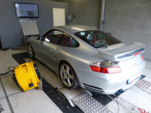 Gray sports car in an engine testing facility