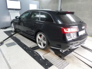 Black Audi van in an engine testing facility